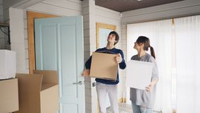 De nieuwe eigenaars van mooi huis gaan binnen met karton dozen, het kijken rond met opwinding en het kussen stock videobeelden