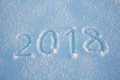 De nieuwe jaren ondertekenen 2018, met de hand geschreven op verse sneeuw Stock Fotografie