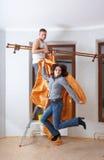 De nieuwe kolonisten probeert op nieuwe gordijnen aan eaves Stock Fotografie