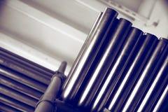 De nieuwe metaalpijpen, met chroom plateerden deklaag, liggen op opslagplanken Conceptenachtergronden van de metaalindustrie De r royalty-vrije stock afbeelding