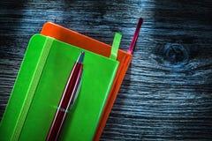 De nieuwe pen van bureaunotitieboekjes op houten raad royalty-vrije stock fotografie