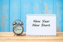 De nieuwe tekst van het jaren Nieuwe Begin op notitieboekje en retro wekker op lijst en exemplaarruimte stock afbeelding