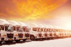De nieuwe vloot van de transportvrachtwagen parkeert engte bij yard met zonsondergang stock foto's