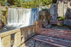 De Nieuwe waterval en de banken van Athos voor rest toeristen Stock Foto's