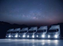 De nieuwe witte vloot van de transportvrachtwagen parkeert bij nacht met milkyway astronomie stock foto's