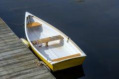 De nieuwere gele en witte roeiboot zit vastgelegd op een kalme stille harbr royalty-vrije stock foto