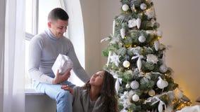 De nieuwjaar` s Vooravond, meisje zit naast echtgenoot met doos dichtbij venster in woonkamer op achtergrond verfraaide Kerstmisb stock videobeelden
