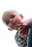 De nieuwsgierige baby kijkt over het wapen van een stoel Stock Foto's