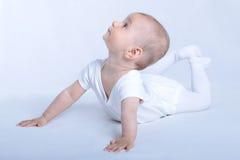 De nieuwsgierige baby op wit kijkt omhoog Stock Afbeeldingen