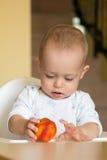 De nieuwsgierige babyjongen onderzoekt een perzik Royalty-vrije Stock Foto's