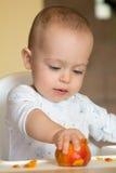 De nieuwsgierige babyjongen onderzoekt een perzik Stock Fotografie