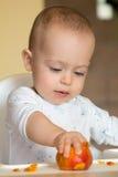 De nieuwsgierige babyjongen onderzoekt een perzik Stock Afbeeldingen