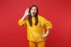 De nieuwsgierige jonge vrouw in gele bontsweater luistert hoorzitting met geïsoleerd handgebaar af dichtbij oor over heldere rode royalty-vrije stock afbeelding