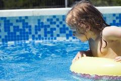 De nieuwsgierige veiligheid van het peuterkind in een zwembad stock afbeeldingen