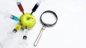 De nitraten, de pesticiden, de fungiciden en andere chemische producten worden ingespoten in een groene appel met een spuit Dicht stock foto