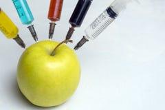 De nitraten, de pesticiden, de fungiciden en andere chemische producten worden ingespoten in een groene appel met een spuit Niet- royalty-vrije stock fotografie