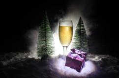 De Noche Vieja el fondo de la celebración con pares de flautas y de botella de champán con el árbol de navidad en nieve en fondo  Imágenes de archivo libres de regalías