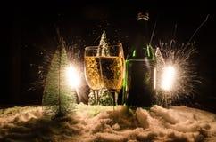 De Noche Vieja el fondo de la celebración con pares de flautas y de botella de champán con el árbol de navidad en nieve en fondo  Foto de archivo libre de regalías