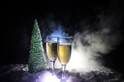 De Noche Vieja el fondo de la celebración con pares de flautas y de botella de champán con el árbol de navidad en nieve en fondo  Imagen de archivo