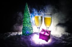 De Noche Vieja el fondo de la celebración con pares de flautas y de botella de champán con el árbol de navidad en nieve en fondo  Imagenes de archivo