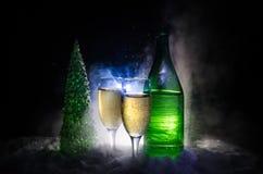 De Noche Vieja el fondo de la celebración con pares de flautas y de botella de champán con el árbol de navidad en nieve en fondo  Imagen de archivo libre de regalías