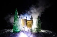 De Noche Vieja el fondo de la celebración con pares de flautas y de botella de champán con el árbol de navidad en nieve en fondo  Fotos de archivo