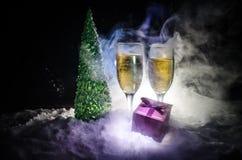 De Noche Vieja el fondo de la celebración con pares de flautas y de botella de champán con el árbol de navidad en nieve en fondo  Fotografía de archivo