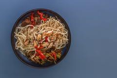 De noedels met zeevruchten, salade, Spaanse peper en gebraden paddestoelen in een traditioneel porselein plateren op een blauwe l royalty-vrije stock foto's