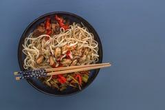 De noedels met zeevruchten, salade, Spaanse peper en gebraden paddestoelen in een traditioneel porselein plateren op een blauwe l stock fotografie