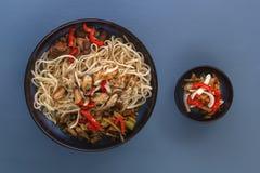 De noedels met zeevruchten, salade, Spaanse peper en gebraden paddestoelen in een traditioneel porselein plateren op een blauwe l stock foto
