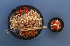 De noedels met zeevruchten, salade, Spaanse peper en gebraden paddestoelen in een traditioneel porselein plateren op een blauwe l stock afbeeldingen
