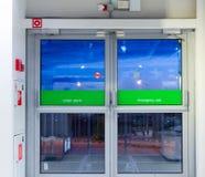 De nooduitgang van de glasdeur aan een straat Duisternis met verlichting Royalty-vrije Stock Fotografie