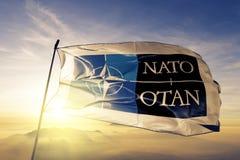 De Noordatlantische Verdragsorganisatienavo OTAN embleem stof die van de vlag de textieldoek op de hoogste mist van de zonsopgang vector illustratie