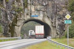 De Noorse rotsachtige tunnel van de bergweg met zware vrachtwagens Stock Fotografie