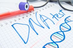 De nota etiketteerde DNA-test en DNA-de formule ligt naast reageerbuizen met bloed, biologisch materiaal en glazen DNA-test of an royalty-vrije stock fotografie