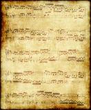 De nota's van de muziek over oud document stock afbeeldingen