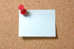 De nota van de post-it met punaise op corkboard stock afbeelding