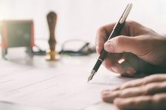 De notaris ondertekent wettelijk contract Zakenman die in bureau werkt royalty-vrije stock foto's