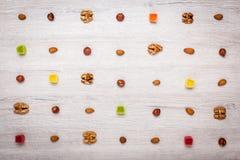 De noten, de amandelen, de hazelnoten en het geleisuikergoed op een lichte houten oppervlakte voerden met symmetrische rijen Mooi Royalty-vrije Stock Fotografie