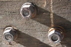 De noten - en - bouten op oud stuk van woden Stock Foto's