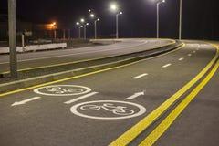 De Noteringen en de Tekens van de fietsweg Verlichte die de reissteeg van de fietssteeg voor fietsers met bestratingsnoteringen w royalty-vrije stock foto's