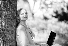 De notulen voor ontspannen Het meisjeswerk met laptop in park zit op gras Onderwijstechnologie en Internet-concept naughty stock foto