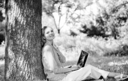 De notulen voor ontspannen Onderwijstechnologie en Internet-concept Het meisjeswerk met laptop in park zit op gras naughty royalty-vrije stock afbeeldingen