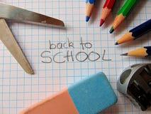 De nouveau à l'école écrite au milieu du matériel d'école images libres de droits