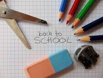 De nouveau à l'école écrite au milieu du matériel d'école photos stock