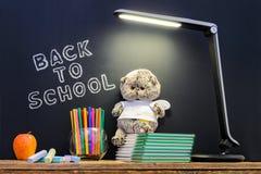 De nouveau à l'école concepty avec l'écriture sur le tableau noir et le bureau, pomme, livres, articles Photos stock