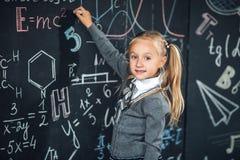 De nouveau à l'école ! Dessin de fille sur le tableau vide avec des formules d'école à l'école L'enfant étudie dans la salle de c photographie stock libre de droits