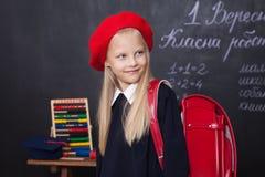 De nouveau à l'école ! La petite fille se tient à l'école avec un sac à dos rouge L'écolière répond à la leçon L'enfant étudie da image libre de droits