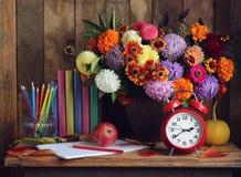 De nouveau à l'école Réveil, bouquet, pommes, et livres sur le t Photo stock