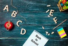 De nouveau à l'école ! Un bureau du ` s d'étudiant sur un conseil pédagogique, un fond en bois foncé fait de conseils Concept d'é Images stock